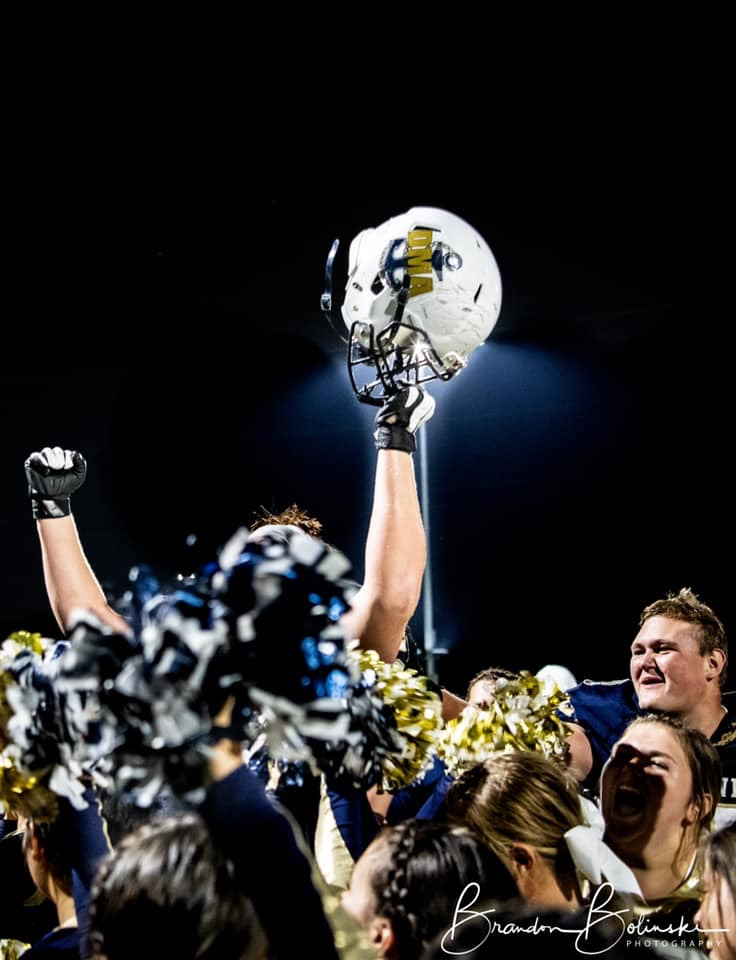 a dma football player raises his dma football helmet high in the air as he is surrounded by his happy peers
